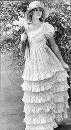 A Model Wears A White Cotton Frilly Dress From Laura Ashley.
