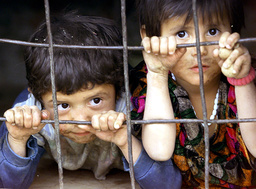 TAJIK CHILDREN LOOK OUT FROM WINDOW OF THEIR HOME IN TEH VILLAGE OF SURHAK CHASHMA