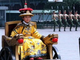 CHINESE GIRL DRESSED IN EMPERORS CLOTHING SITS IN BEIJING