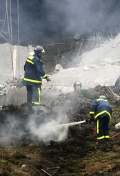 Firemen work at one of the parking lots of Madrid's Barajas airport