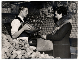 Boxer Johnny Quill serving customer in a greengrocer's shop - 1935