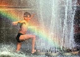A UKRAINIAN BOY ENJOYS BATHING IN A FOUNTAIN