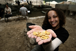 British volunteer holds coins she helped unearth during excavations in Jerusalem
