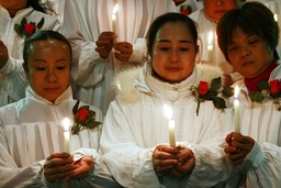 Catholics hold candles on Christmas eve in a church in Suining