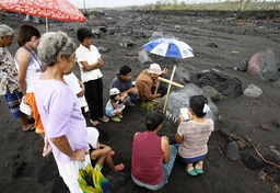 A Filipino family plants candles and offers prayers in Padang village
