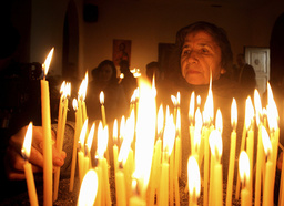 Worshippers light candles on Christmas day at church in Tirana