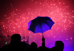 Spectators watch a fireworks display amidst the rain during a New Year's eve countdown in Fort Bonifacio, Metro Manila
