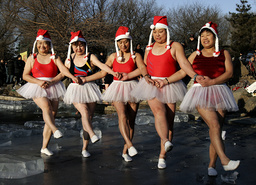 People dressed in Santa Claus costumes dance as they celebrate the upcoming Christmas Day at a park in Shenyang
