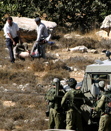 TWO PALESTINIANS CARRY BODY OF ISLAMIC JIHAD MILITANT KILLED DURING ISRAELI ARMY OPERATION IN DURA