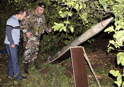 Lebanese army personnel inspect one of eight rockets found in a field in Naqoura village