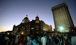 People gather outside the fully lit-up Taj Mahal hotel, one of the sites of the last month's militant attacks, during New Year celebrations in Mumbai