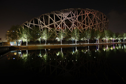 National Stadium, also known as Bird's Nest, is seen reflected in a lake during Earth Hour at Olympic Park in Beijing