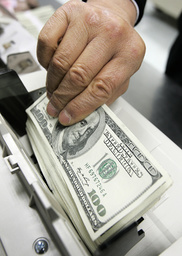 Employee of the Korea Exchange Bank counts dollar notes at the bank's headquarters in Seoul