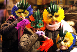 Children with masks blow trumpets as they wait for New Year's Eve festivities to begin in Budapest