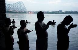 HINDU DEVOTEES PRAY ON HOOGLY RIVER IN CALCUTTA