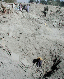 AN AFGHAN YOUTH INVESTIGATES A BOMB CRATER IN KABUL