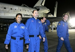 Crewmembers of space shuttle Discovery walk away from the shuttle on the runway at the Kennedy Space Center in Cape Canaveral