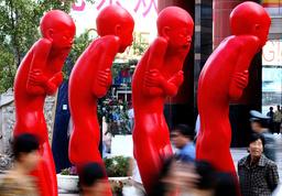 PEDESTRIANS WALK PAST A SCULPTURE NAMED RED MEMORY AT AN ART EXHIBITION IN BEIJING