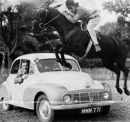 Expert Horsewoman Pat Moss On Silver Leap Jumps Over Her Racing Driver Brother Sir Stirling Moss's Car In The Paddock Of Their Tring Home. Morris Car.