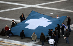 Anti-government protesters hold a huge 19th century Greek flag in front of the parliament during a debate prior to a vote of confidence in Athens