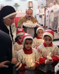 Christian children hold candles during a Christmas mass at a church in Basra