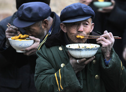 Worshippers eat traditional food as they prepare to take part in the Dajiao Taoist festival in Fengjiashan village