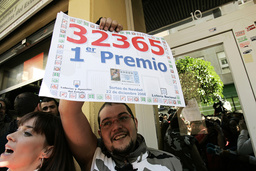 A man celebrates winning a portion of Spain's Christmas lottery as he holds up a banner with the number of the first prize ticket or El Gordo (The fat one) in Torrevieja
