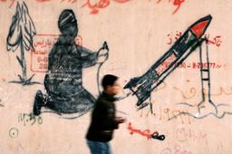 Palestinian boy walks past mural in Gaza
