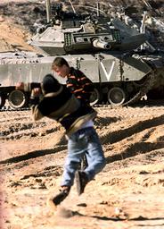 PALESTINIAN BOY THROWS STONES AT ISRAELI TANK IN GAZA STRIP