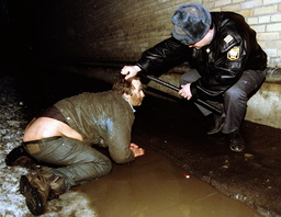 A RUSSIAN POLICEMAN ATTENDS TO DRUNK IN GUTTER