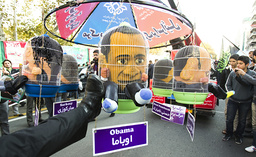 A protester kicks a puppet representing U.S. President Obama during an anti-U.S. gathering in Tehran
