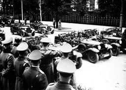 ADOLF HITLER, FOREGROUND, SALUTING MECHANISED UNITS OF THE GERMAN ARMY DURING A VICTORY PARADE IN WARSAW, OCTOBER 1939.