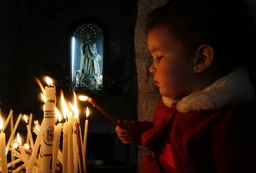 A child lights a candle in the Church of Nativity in Bethlehem