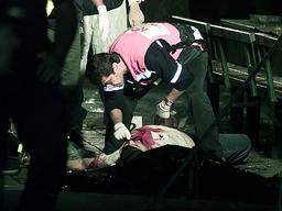 ISRAELI POLICEMAN CHECKS THE BODY OF A VICTIM OF A SUICIDE BOMBING IN RISHON LETZION