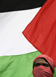 A member of hardliner Islamic Defenders Front (FPI) stands in front of Palestinian flag during a protest in Jakarta