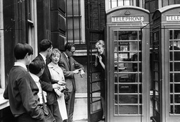 A Young Woman Sticks Out Of A Red Telephone Box Covering The Mouthpiece And Looks At The Long Queue With One Man Looking At His Watch. Posed By Models.