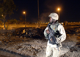 U.S. ARMY SOLDIER GUARDS SPOT WHERE SUSPECTED ROADSIDE BOMB EXPLODED ON THE MAIN HIGHWAY IN BAGHDAD