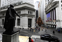 A statue of George Washington looks out over a lightly traveled Wall Street and the New York Stock Exchange in New York
