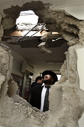 Israeli man looks at classroom damaged after a rocket landed in Beersheba