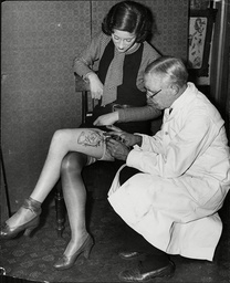 Tattooist Doctor G Burchett Tattooing A Woman's Leg With A Floral Garter.