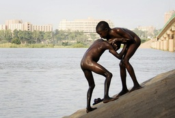 Boys wrestle by the Niger River in Niamey