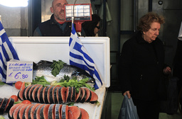 A woman leaves the stall of a fishmonger at a food market in Athens