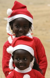 Two Ivorian sisters Malone Toure and Madorsa Toure, dressed in Christmas costumes, play in the streets of Abidjan