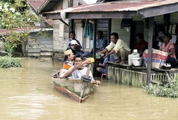 Villagers in a boat distribute food to their flood-affected neighbours in the village of Pelawi