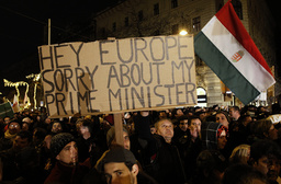 A man holds up a sign during a protest in central Budapest