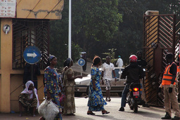 People walk in front of the entrance of the Donka Hospital, where victims of the ebola disease are being treated, in Conakry