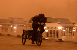 AN OLD MAN STRAINS TO PEDDLE HIS TRICYLCE INTO A SAND STORM IN BEIJING