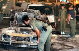 AN ISRAELI SOLDIER EXAMINES THE REMAINS OF A CAR IN HEBRON