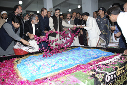 Pakistani Prime Minister Yousaf Raza Gilani (C) scatters rose petals with party supporters and leaders at the grave of their slain leader, former prime minister Benazir Bhutto, ahead of her first death anniversary in Garhi Khuda Bakhsh