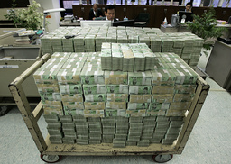 Stacks of ten thousand Korean won bills are placed on a cart and a desk at the headquarters of the Korea Exchange Bank in Seoul
